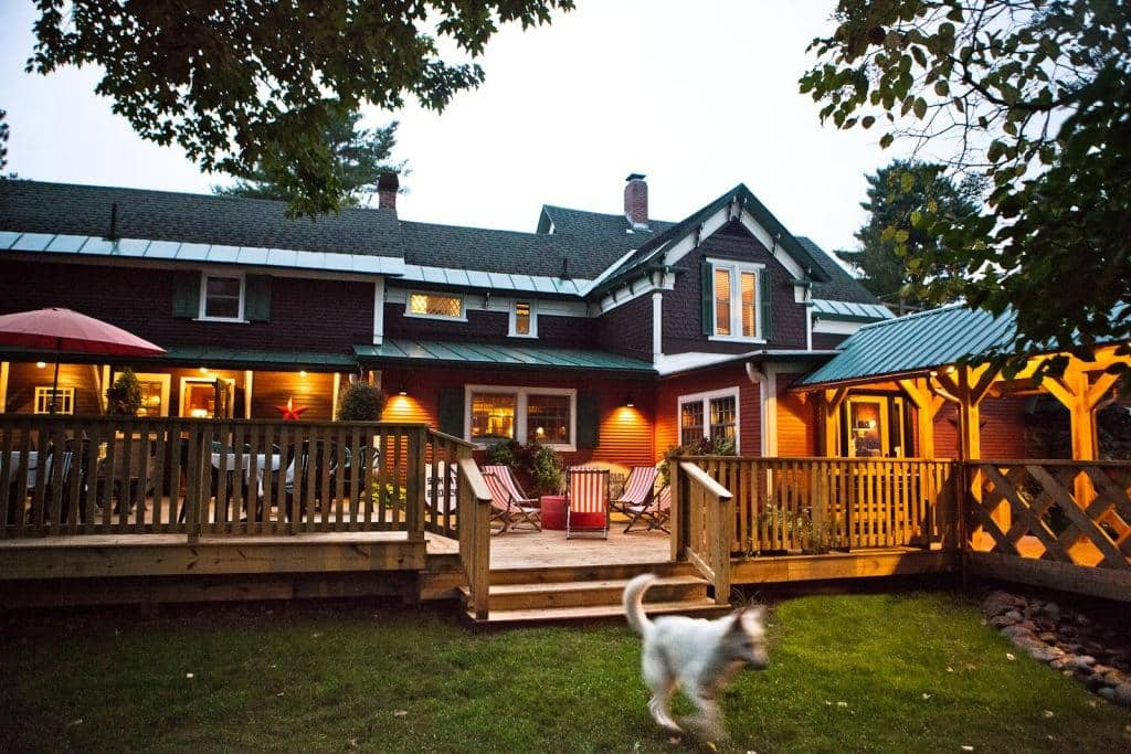 wood deck with seating attached to large building with dog playing in the foreground