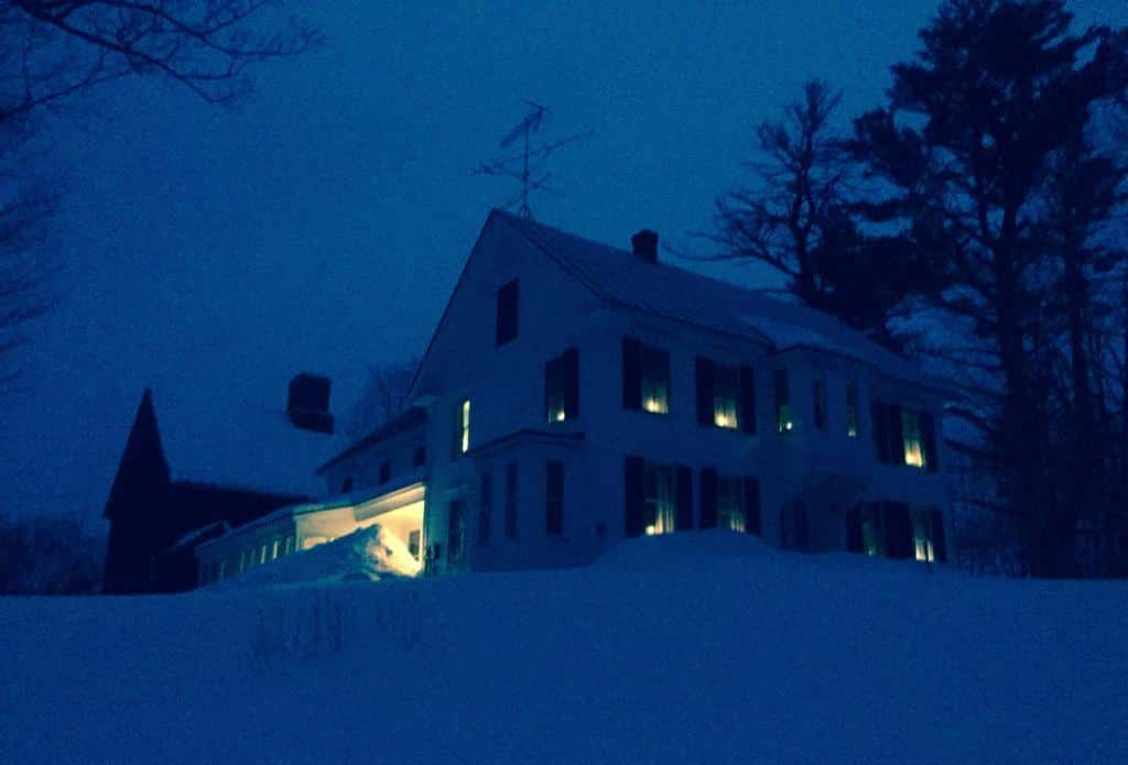 white colonial home atop snow covered hill with lights glowing in each window