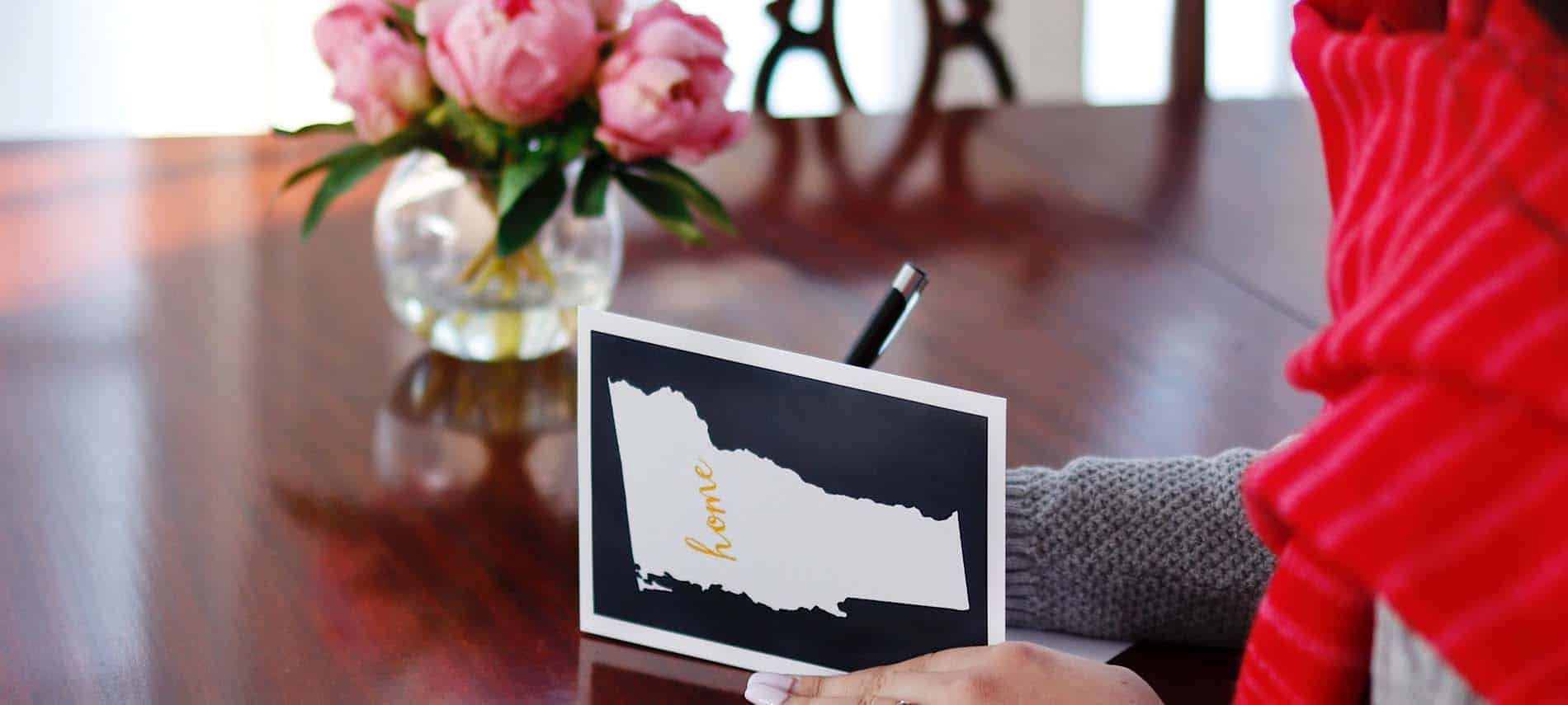 girl writing note on vermont card by vase of peony