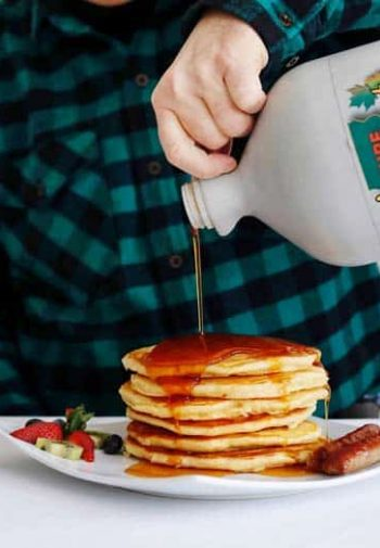 man in vermont flannel shirt pouring gallon of maple syrup on tall stack of pancakes