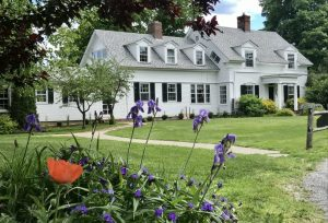 stately white cape style home on a green lawn with purple flowers