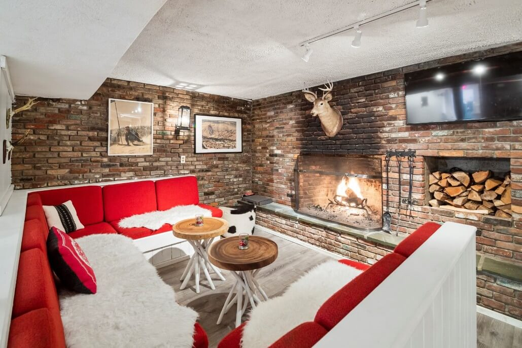 red pit group in front of large fireplace in brick walled room