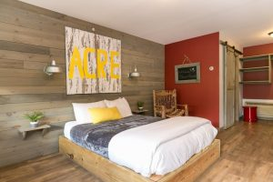 platform bed, wood panel-walled bedroom with artwork on the wall