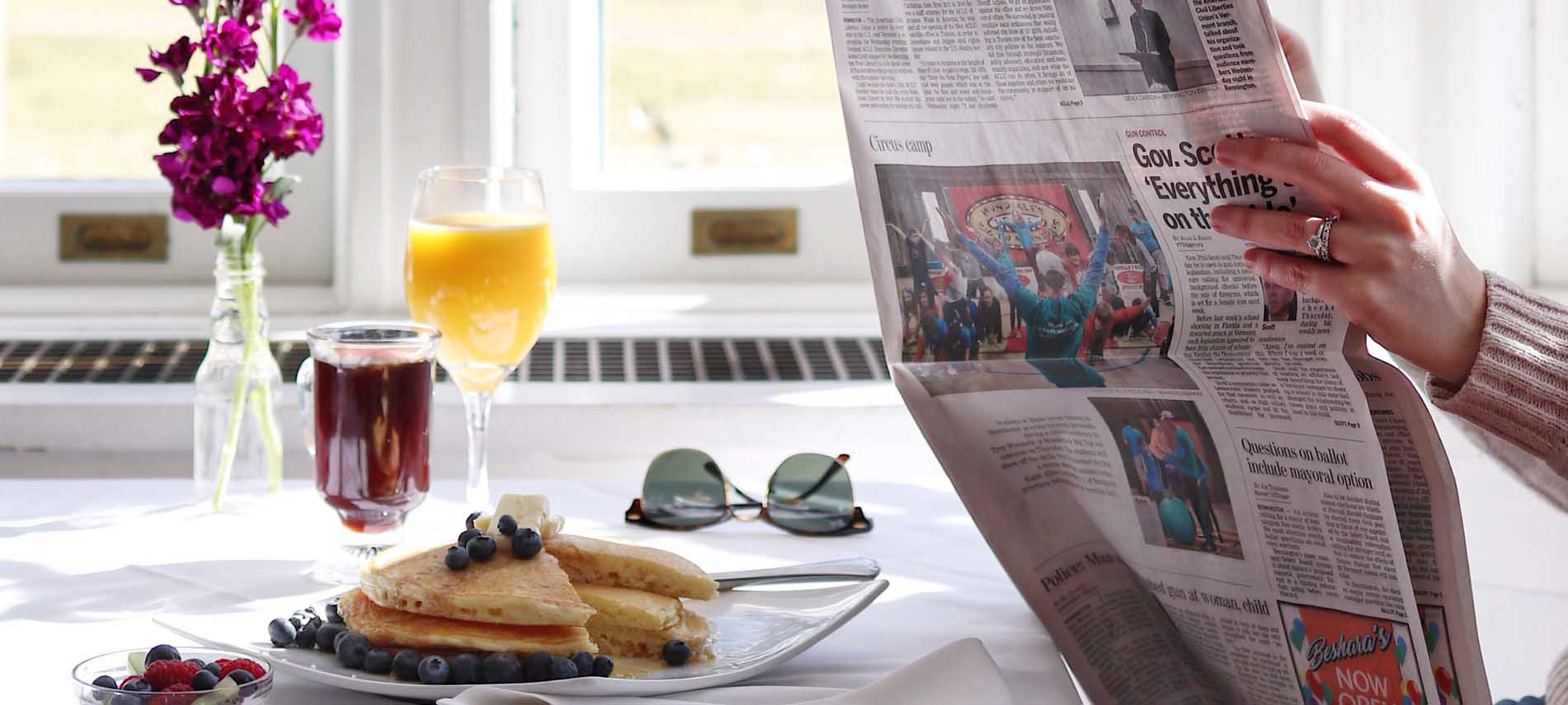 woman reading newspaper in front of plate of blueberry pancakes