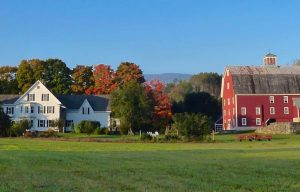 white house and red barn on a grassy plain