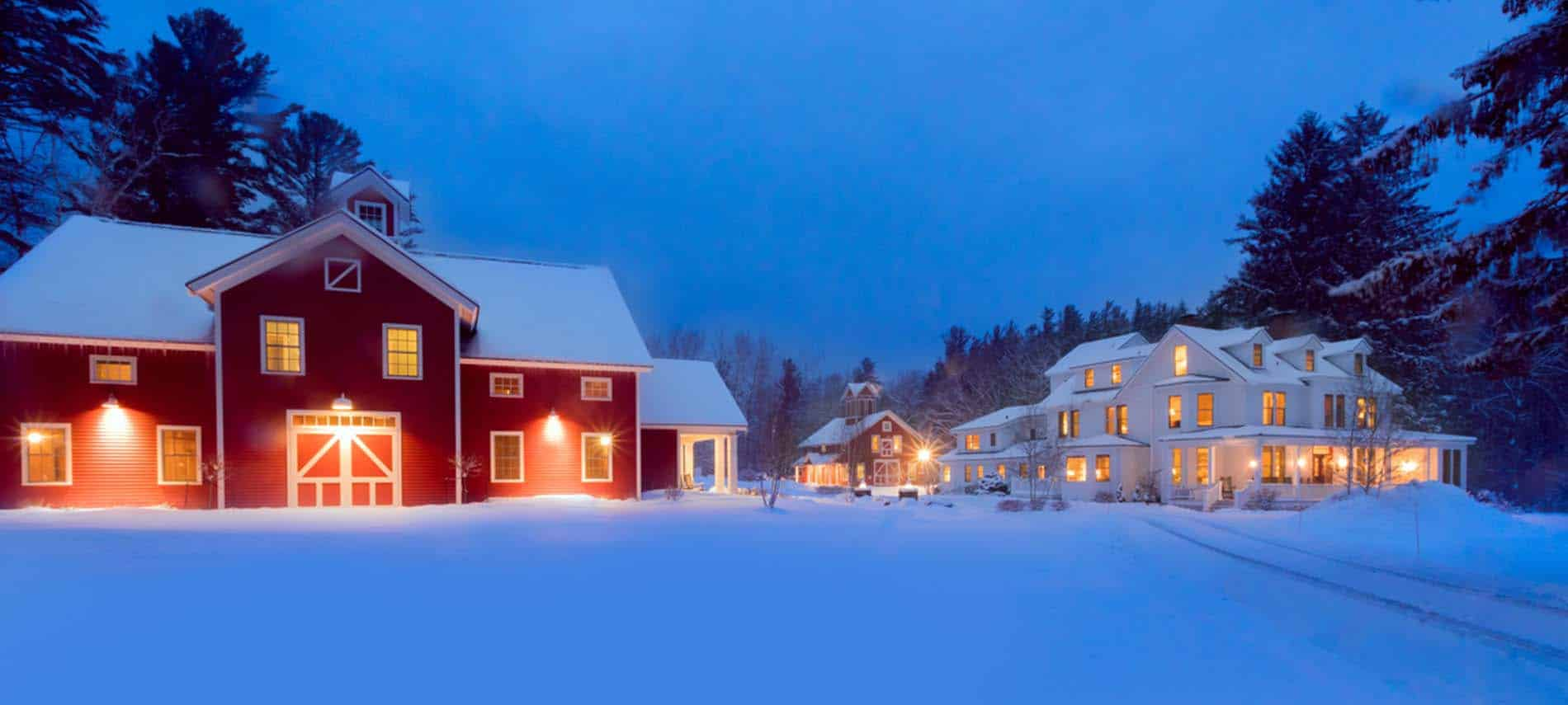 snowy scene at dusk with red barn and inn with glowing lights