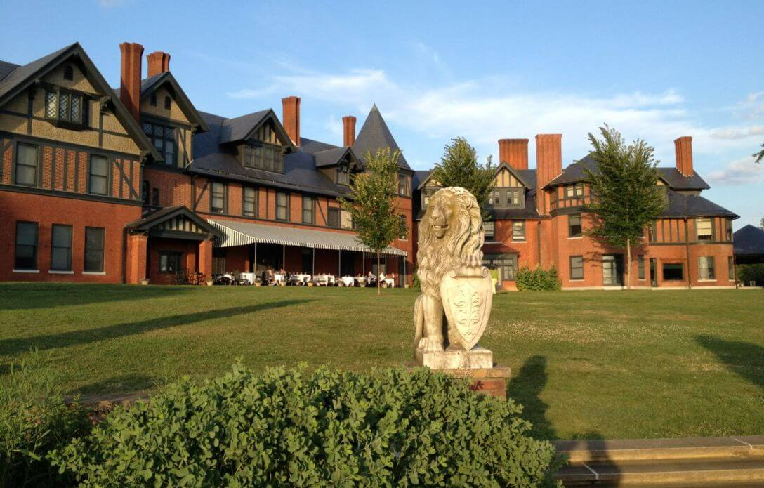 palacial brick building on a green lawn fronted by a lion statue