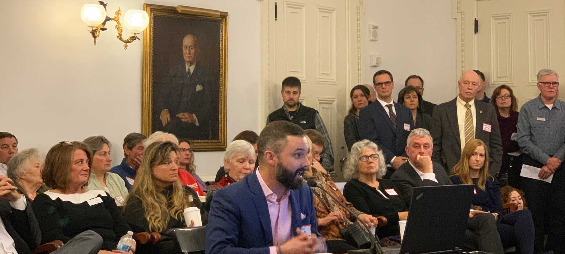 man testifying at vermont state house crowded room