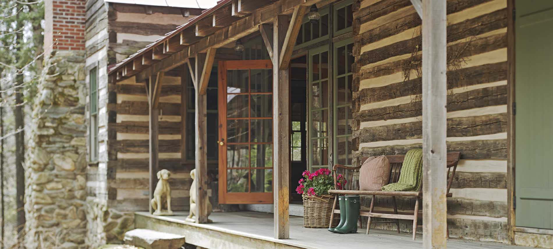 porch of luxury vermont cabin hunter boots and flowers by bench