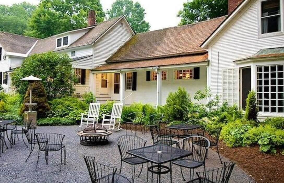 outdoor seating in front of white building with porch