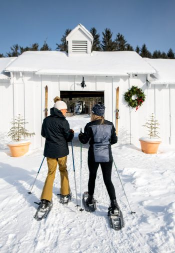 two cross country skiers heading for a barn