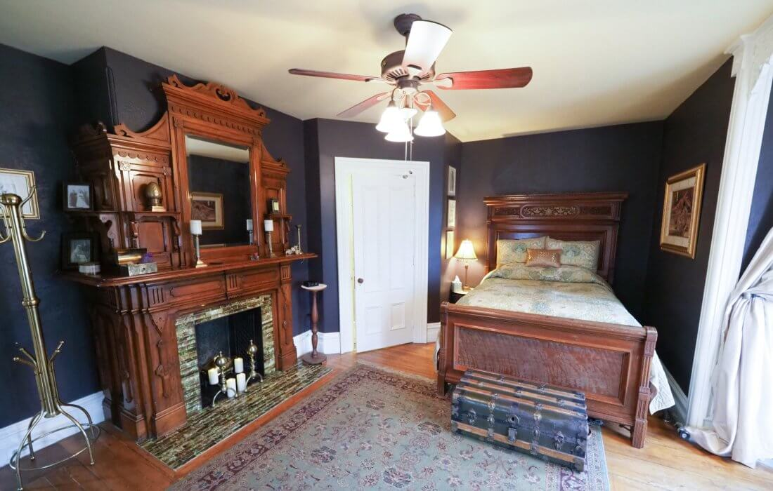 blue bedroom with large wood bed and ornate wood mantle fireplace