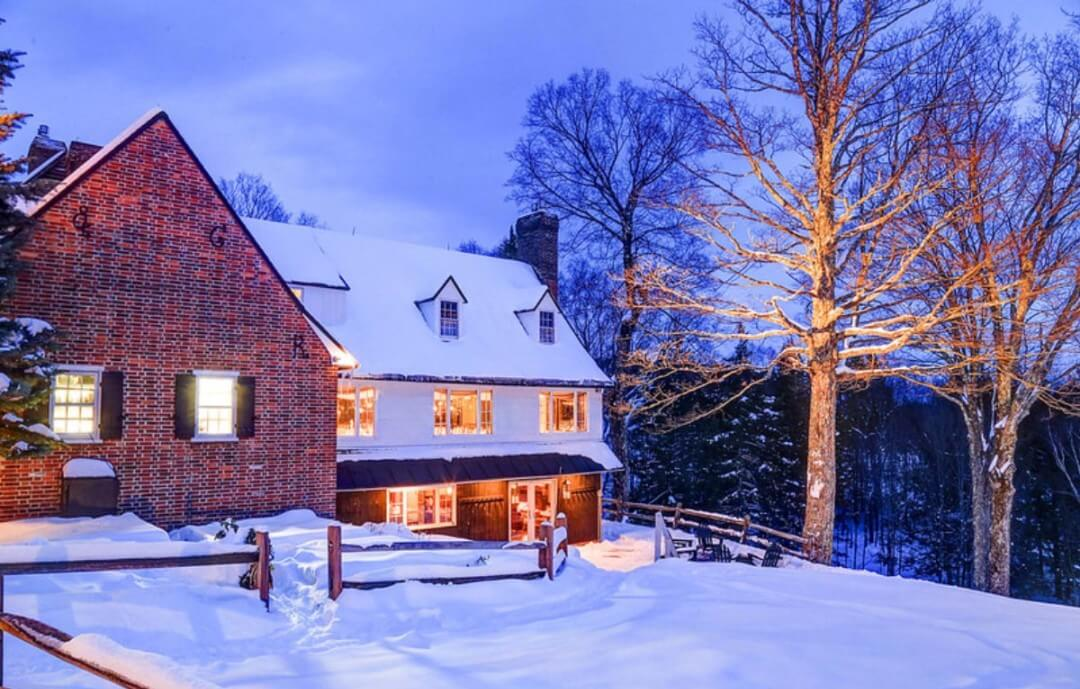 illuminated brick front home with corrale fencing on snow covered land