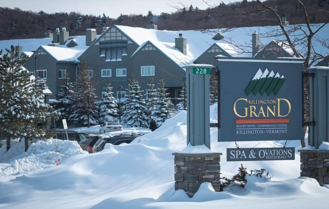 killington resort sign with large ski hotel behind it in winter