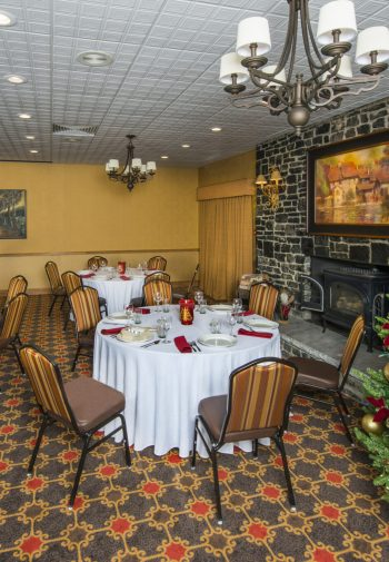Banquet room with individual tables and winter holiday decorations.