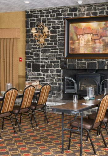 Chairs lined up in rows for a meeting with stone fireplace in the background.