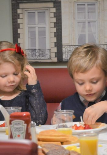 Two blond toddlers share breakfast at a table in the hotel.
