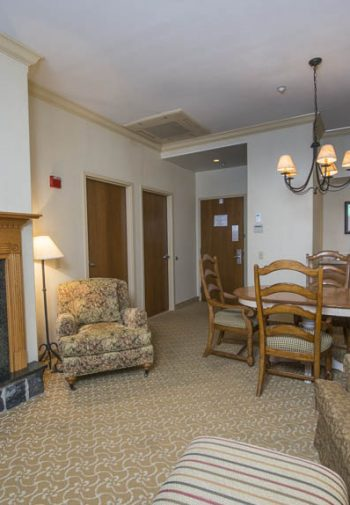 Hotel room suite with sitting area and a gas fireplace.