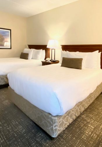 Two double beds with white sheets in a hotel room.