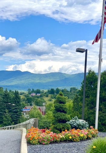 United States and Vermont flags in hotel parking lot with lush green mountain background.