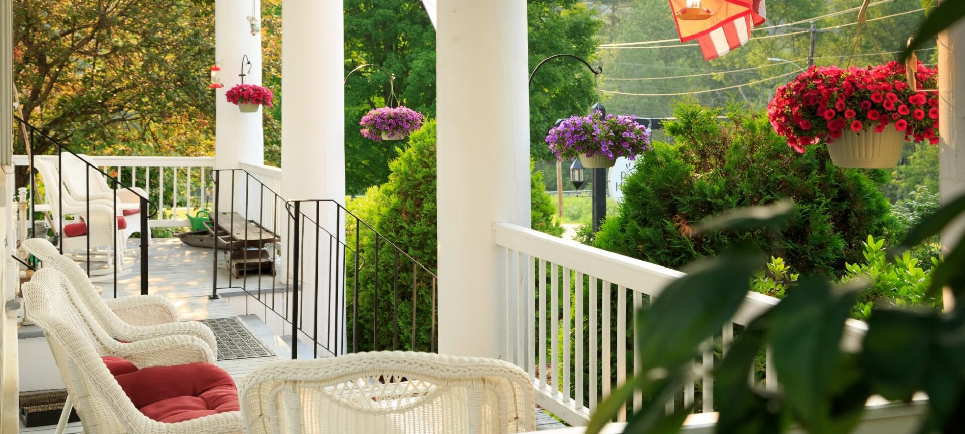 front porch in summer with colorful hanging plants