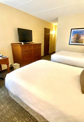 Hotel room of the standard size with television near bed.