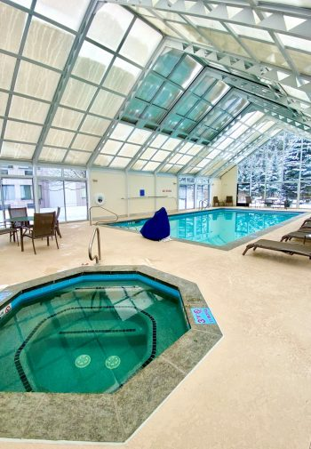 Pool and hot tub with glass roof and cement pool deck.