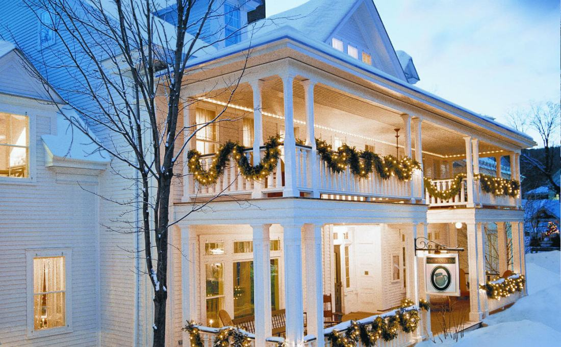 white porches with green garland on a snowy day