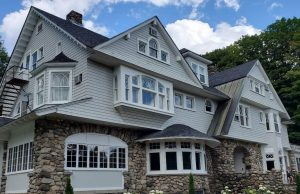 Large gray house with stone foundation