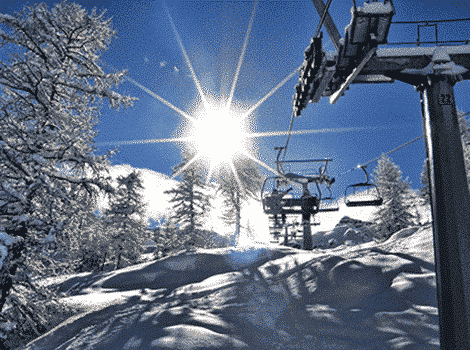 Snow covered slopes with pine trees, a ski lift, and blue skies with the brilliant sun shining through