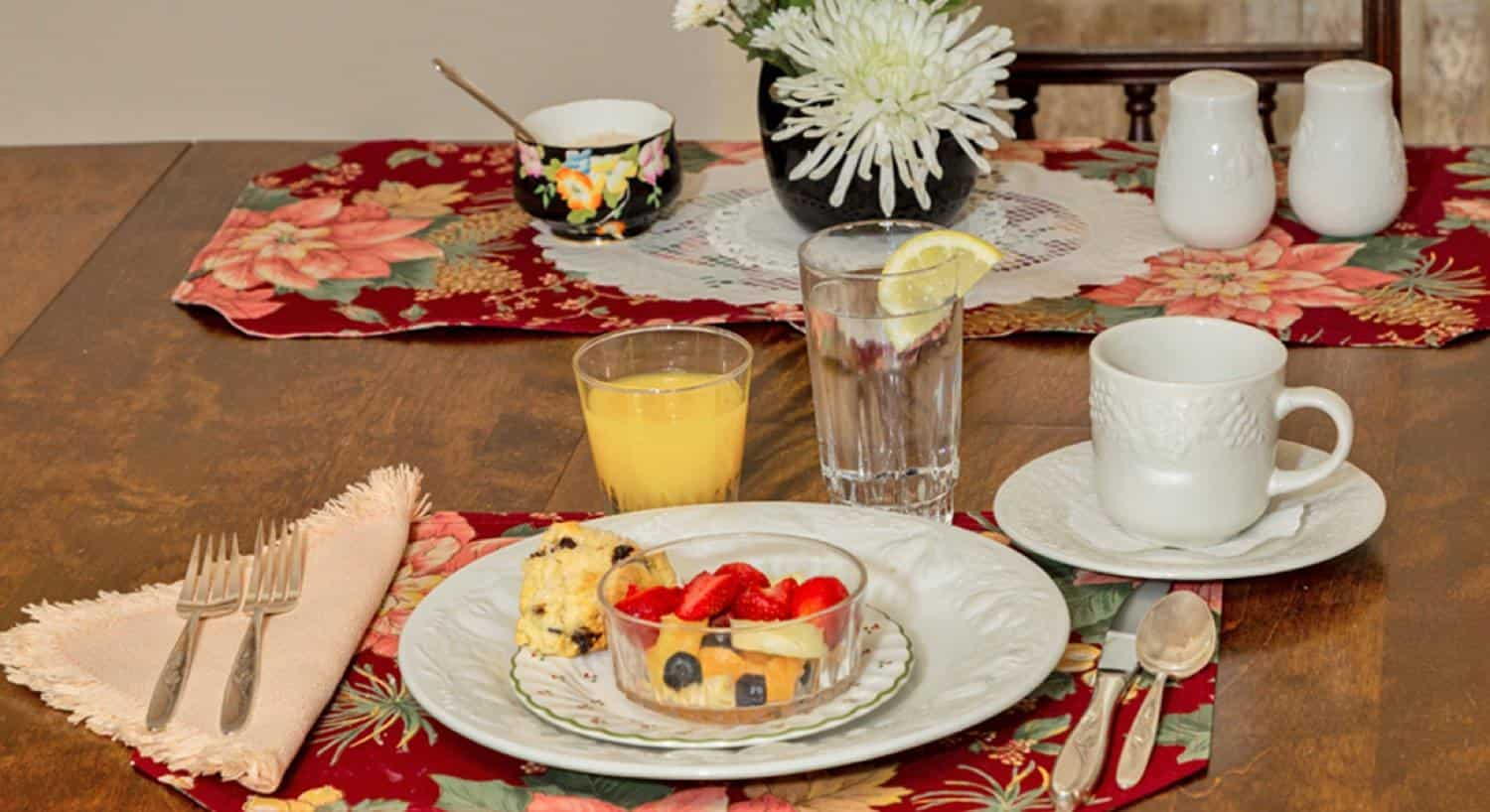 Dining table set with fresh flowers, fruit, scone, juice, lemon water and coffee cup
