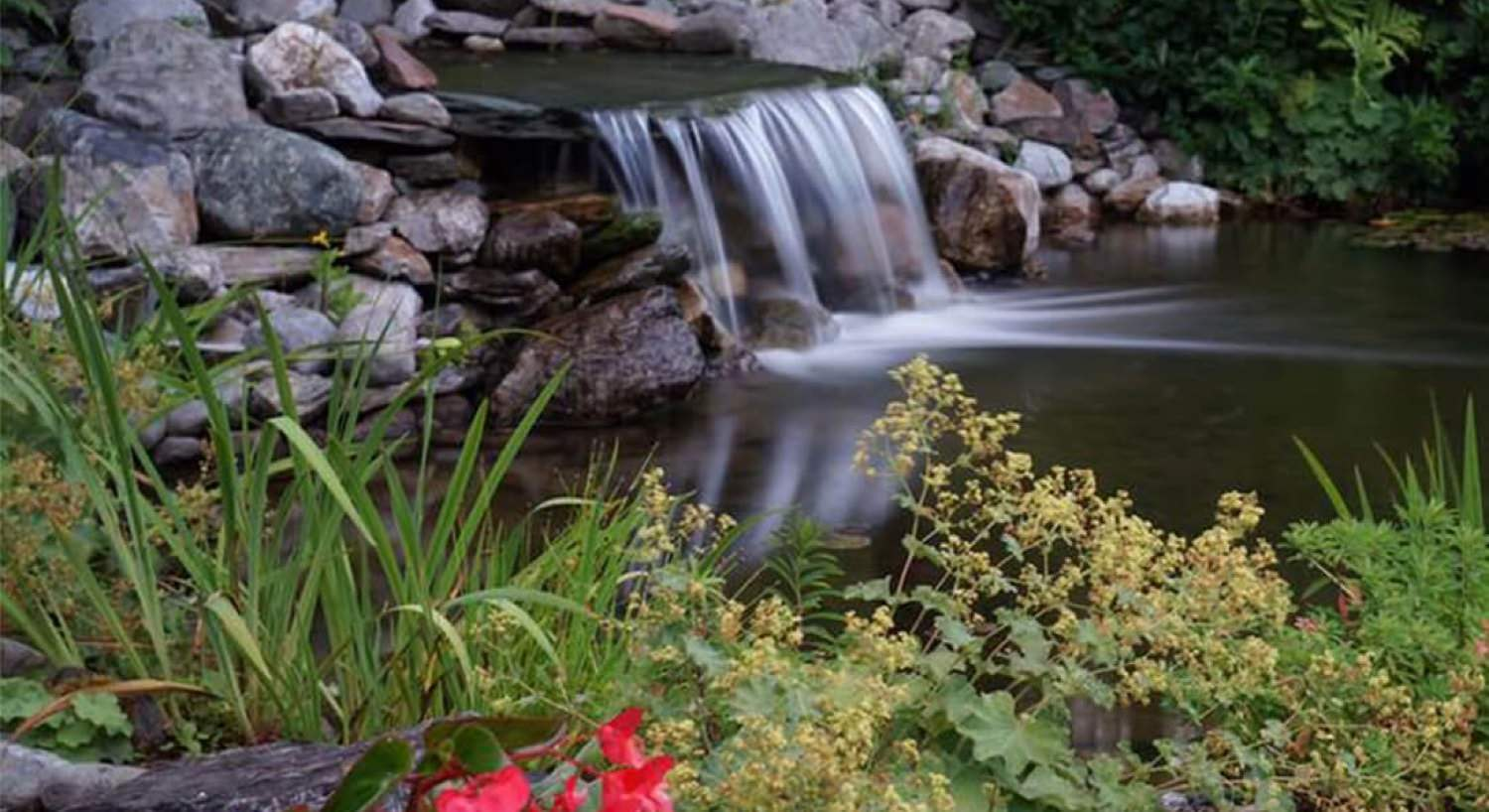 Beautiful small waterfall and pond surrounded by rocks, plants and flowers