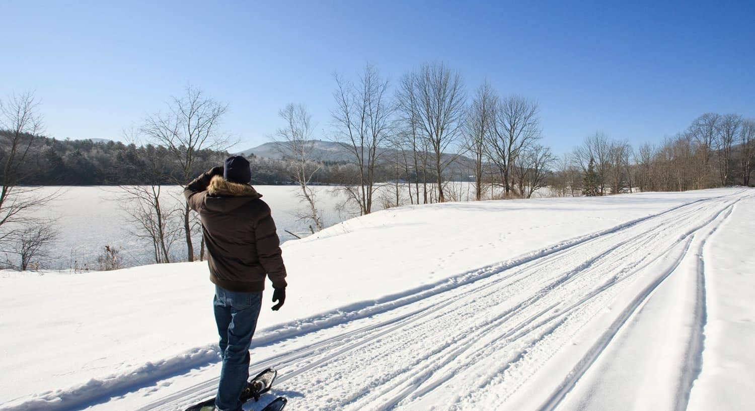 Man wearing cross-country skis on a snowy lane overlooking miles of snow-covered hilly terrain and blue skies