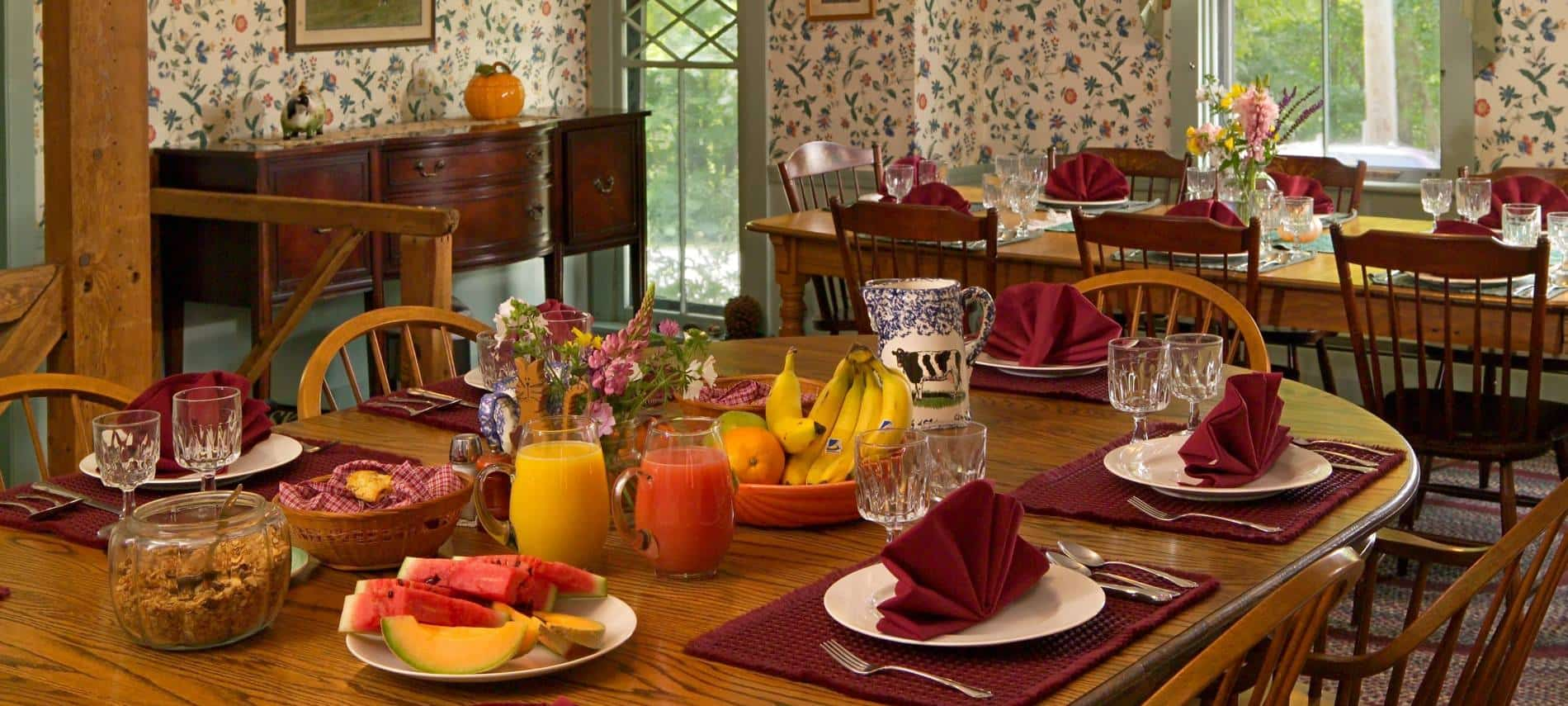 Cozy dining area with papered walls, windows, dining tables and chairs set for breakfast with granola, fruit, juice and flowers