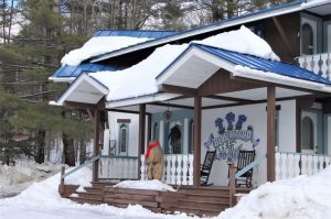 Front view of home painted white and brown with blue metal roof surrounded by snow