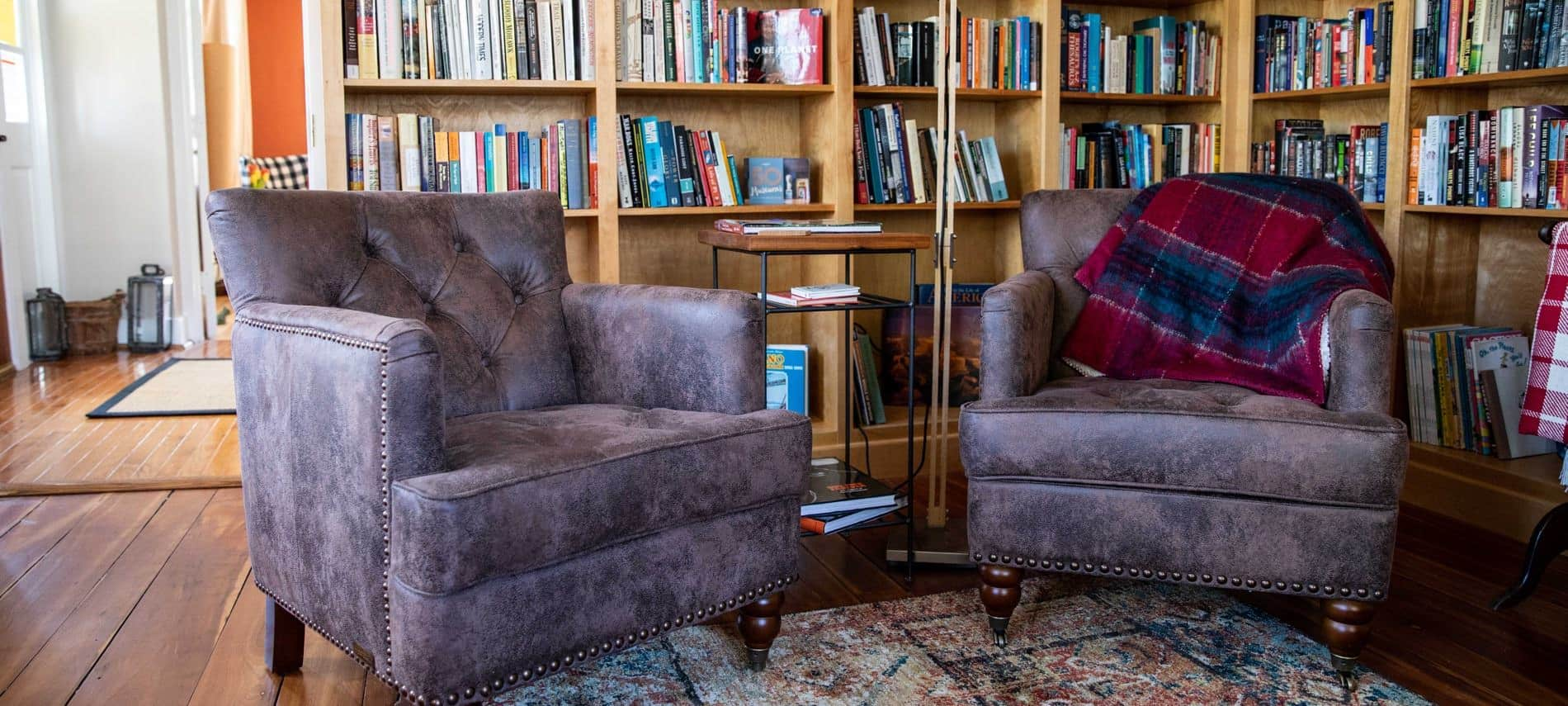 Cozy reading nook with two leather chairs in front of two walls of book-lined shelves