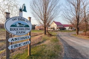Wooden sign for The Inn at Buck Hollow Farm with the home in the background down a dirt driveway