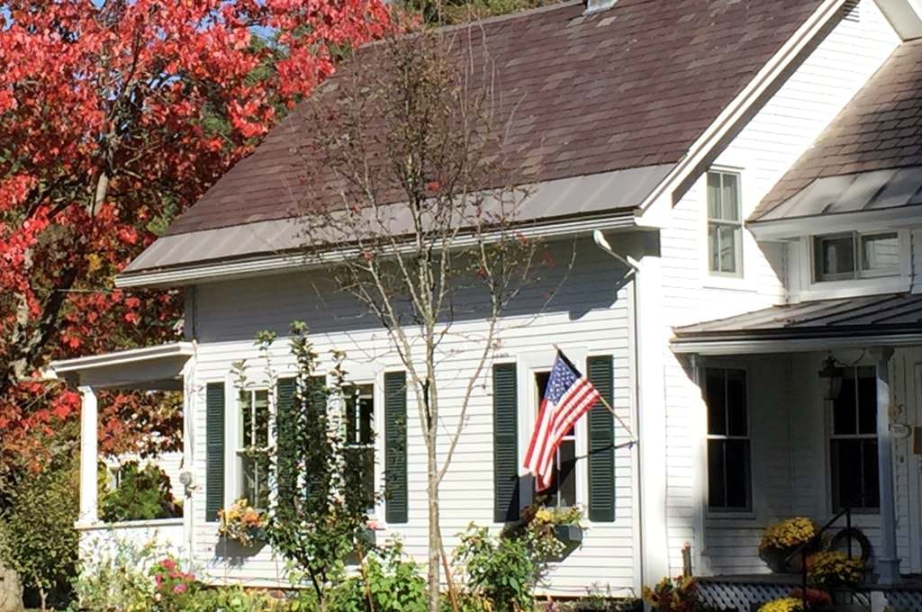 Partial view of home painted white with dark shutters next to a tree with red leaves