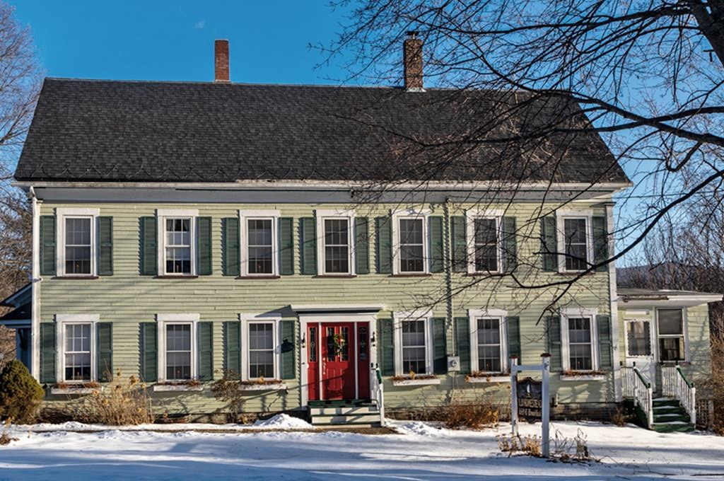 Front view of house painted light green with dark green shutters and red front door