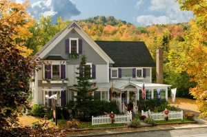 Front view of house painted gray and white with dark purple shutters surrounded by many trees with fall foliage