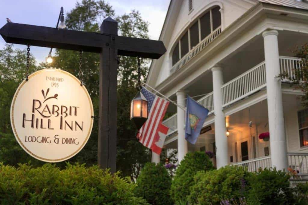 Front view of white house with large Rabbit Hill Inn sign hanging on a wooden post
