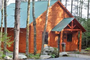 Log cabin with green metal roof surrounded by trees and large rocks