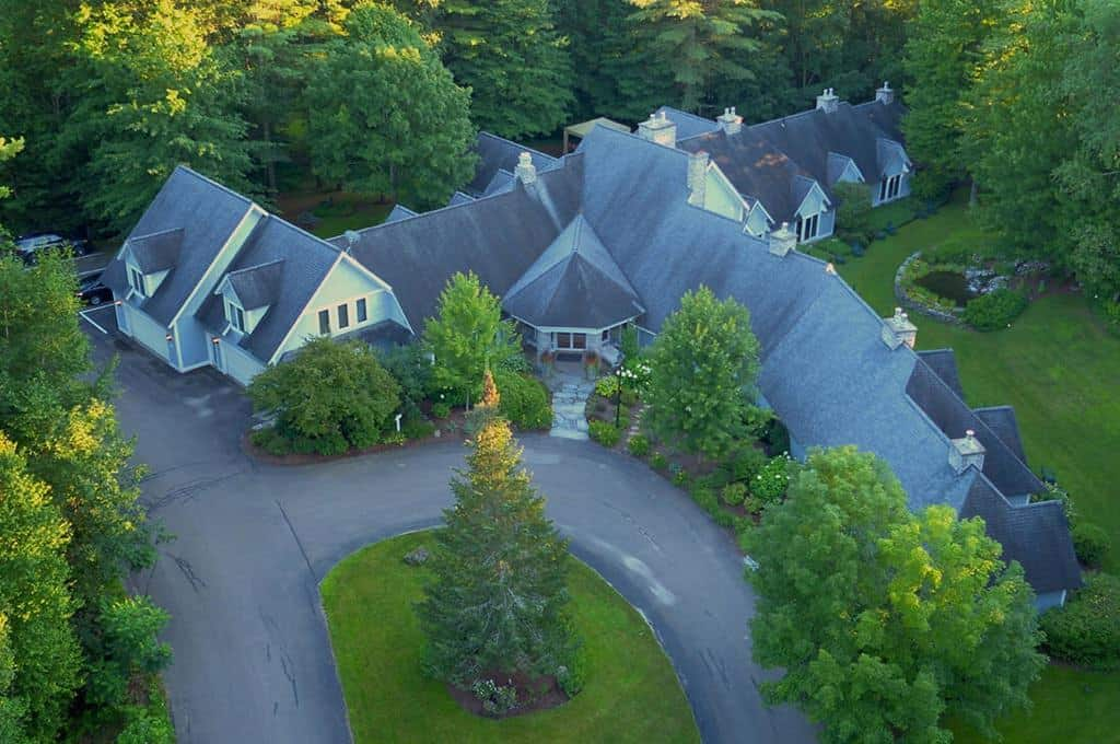 Aerial view of large home surrounded by green grass, trees, and plants
