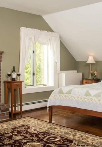 Charming peaceful guest room with slanted ceiling, brick fireplace, raised hearth, wood platform bed, window, wood floors and area rug