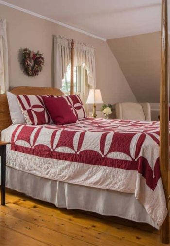 Spacious guest room with several windows, wide plank floors, four poster bed, rocking chair, and upholstered furniture