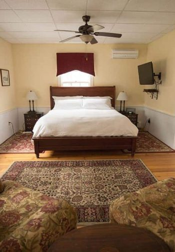 Spacious guest room with creamy walls, wood floors with area rugs, wood bed, nightstands, windows, and upholstered chairs