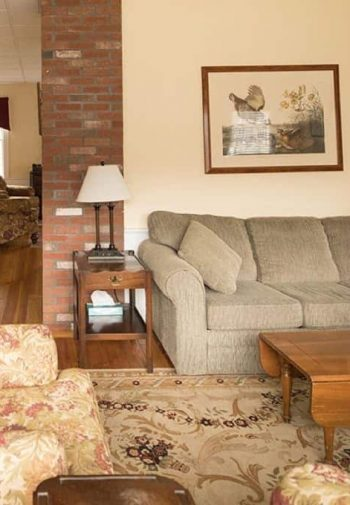 Cozy common area with warm beige walls and wood floors, upholstered sofas and chairs, and side tables