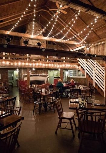 Rustic vaulted barn with twinkle lights hanging from the rafters and several wood tables and chairs set for a meal
