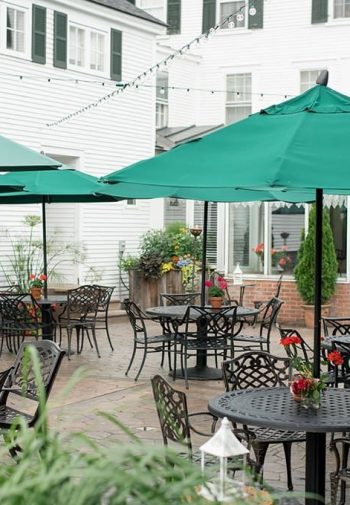 Exterior view of Grafton Inn with large patio, several black patio tables and chairs with turquoise green umbrellas