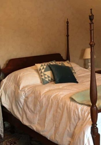 Guest room with slanted ceiling, four poster twin bed, and two nightstands with lamps